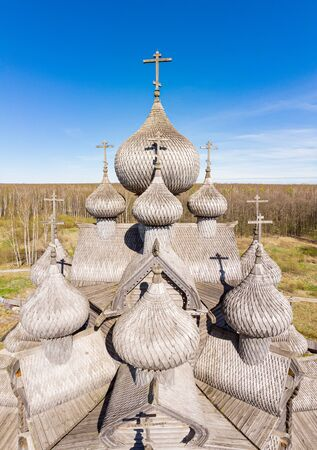 Beautiful Aerial view to traditional Russian village with orthodox wooden chapel and bell tower in Bogoslovka manor. Pokrovskaya multi domed church holy virgin in Easter day. St. Petersburg, Russia.