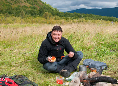 adult sandwich: Smiling man eating red caviar in the open air
