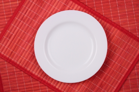 the net empty white plate on a red tablecloth top view of wooden photo