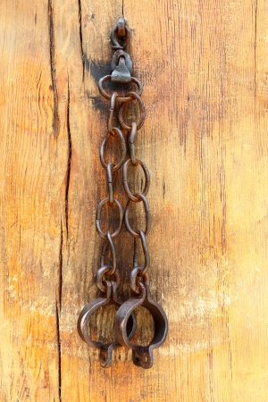 Metal forged shackles on a chain hanging on a wooden wall photo