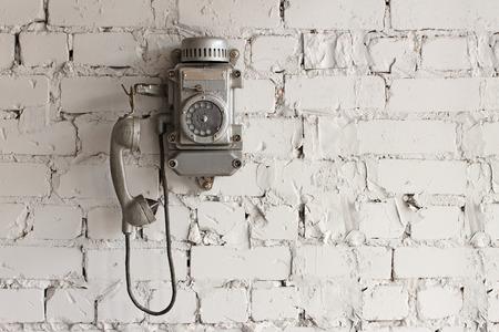 metallic telephone mounted on a light gray brick wall photo