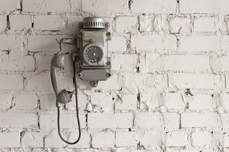 metallic telephone mounted on a light gray brick wall
