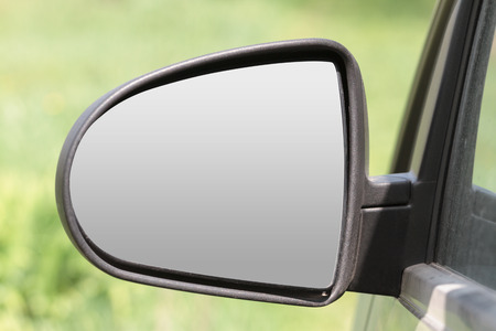 car rearview mirror triangular shape on a blurred green background