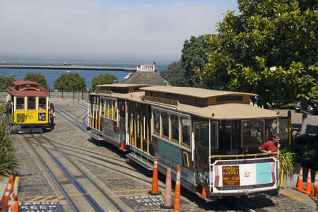 Historic wooden cable car riding the steep streets of San Francisco, looking out over the blue ocean bay
