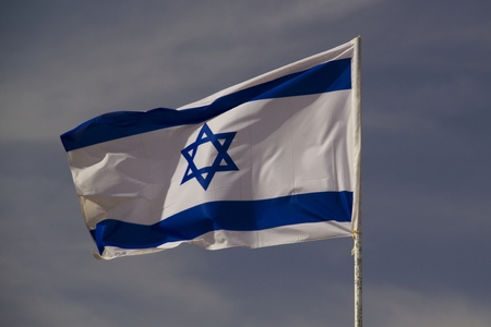 The blue and white national flag of Israel blowing in the wind  photo