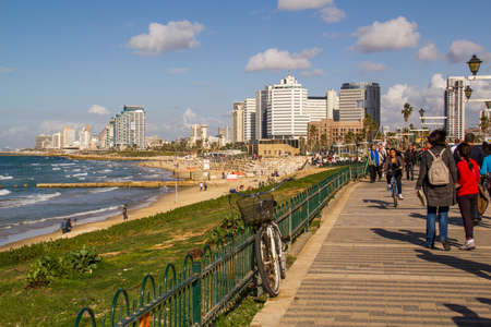 Tel Aviv, Israel - December 20, 2014: coast beach with promenade on the background of the city.Tel Aviv- Jaffa promenadeTourists and locals are enjoying a sunny day along the Tel Aviv promenade on December 20,2014 .Israel