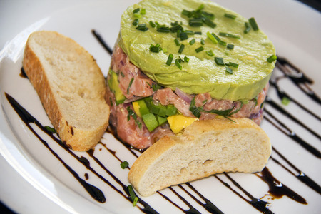 Raw salmon chopped and mixed with pepper and onion sour cream, Avocado cream and chives as garnish photo