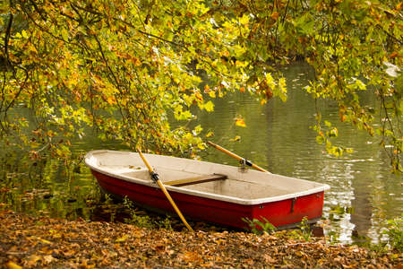 Autumn park with red boat in the pond photo