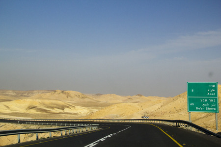 Modern Desert Highway with mountains background and blue sky. The Dead Sea Area in Israel with road Sign to Arad and Beer Sheva