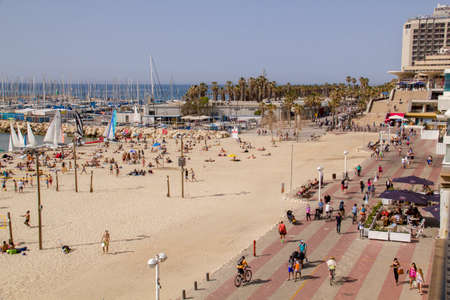 TEL AVIV - APRIL 7th,2015: The beach in Tel Aviv, packed with people on a hot day. Some are in the water, some are biking or walking, on  APRIL 7th 2015, in Tel Aviv, Israel.