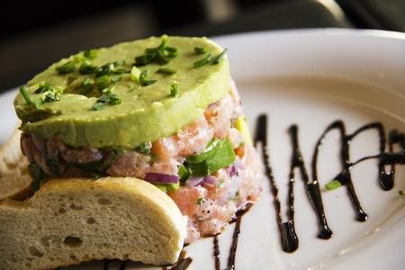 Salmon Tartar with Avocado on the plate Stock Photo