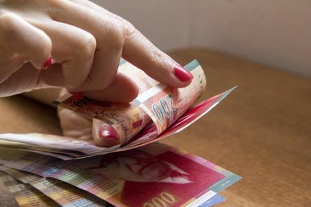 sheqel: Woman counting money - Israeli New Sheqel banknotes. Stock Photo