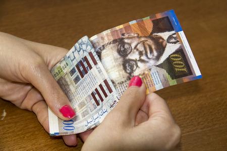 bank activities: Woman counting money - Israeli New Sheqel banknotes. Stock Photo
