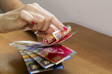 buisiness: Woman counting money - Israeli New Sheqel banknotes. Stock Photo