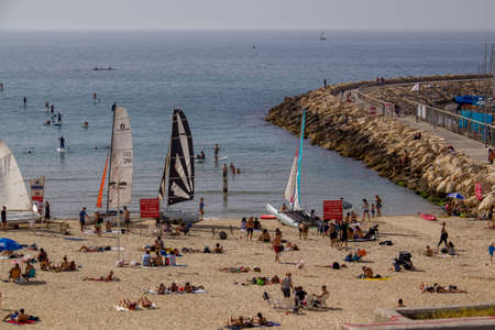 dwelling: TEL AVIV - APRIL 7th,2015: The beach in Tel Aviv, packed with people on a hot day. Some are in the water, some are sunbathing or shade dwelling, on  APRIL 7th 2015, in Tel Aviv, Israel.
