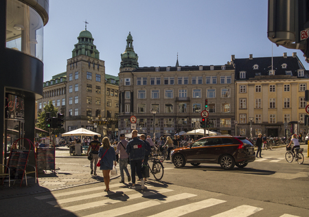 COPENHAGEN, DENMARK - SEPTEMBER 5:Pedestrians in central Copenhagen Gammeltorv (Old Square) and Caritas Fountain. Denmark Europe on September 5, 2016 in Copenhagen, Denmark.The square and fountain are oldest in Copenhagen. They are part of Stroget pedestr