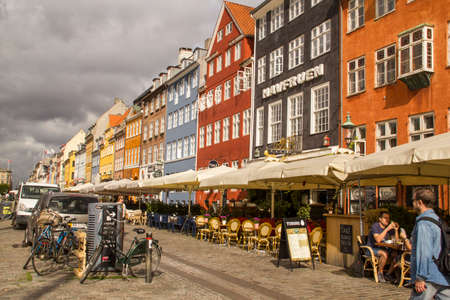 townhouses: Copenhagen,Denmark - September 02 2016: Iconic Nyhavn waterfront lined by colourful townhouses in Copenhagens historic district.Tourist enjoy al fresco dining and watching ships drift down the waterway. Editorial