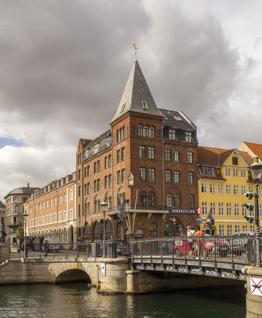 Copenhagen,Denmark - September 02 2016: Iconic Nyhavn waterfront lined by colourful townhouses in Copenhagens historic district.Tourist enjoy al fresco dining and watching ships drift down the waterway. Editorial