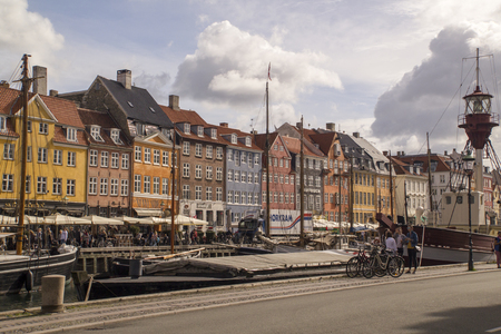 townhouses: Copenhagen,Denmark - September 03 2016: Iconic Nyhavn waterfront lined by colourful townhouses in Copenhagens historic district.Tourist enjoy al fresco dining and watching ships drift down the waterway.