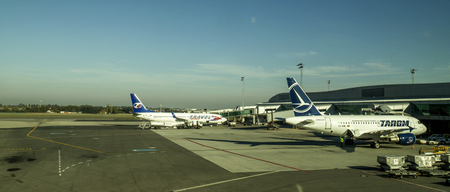 Prague, Czech Repiblic, September 02,2015:Airplanes of different airlines stand on the runway of the airport Ruzine in Prague, Czech Repiblic, Technitian from Ground crew working below a passenger airplane.Panoramic View