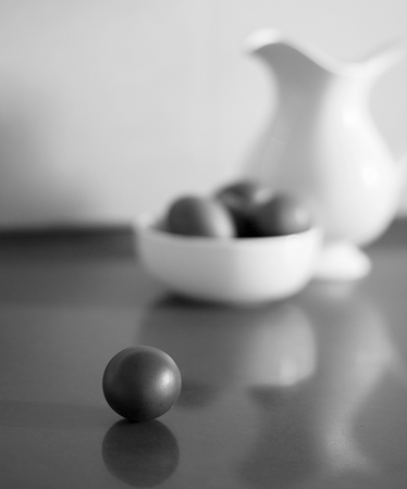 Black and White Still life with brown eggs and white pitcher.Focus on the single egg.Shallow DOF