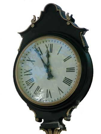 An isolated clock displaying six minutes to midnight