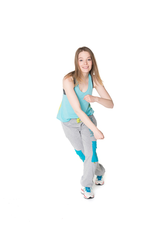 Young, pretty, natural looking girl in sport t-shirt and jogging pants having fun dancing. Full body studio shot, pure white background Stock Photo