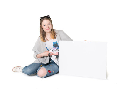 Young beautiful girl in casual clothes holding cardboard, isolated white background