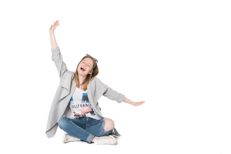 Young beautiful girl in casual clothes sitting on floor, studio shot isolated, pure white background
