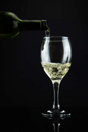 wine bottle and glass, black background