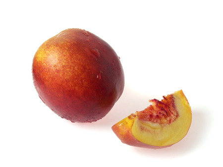 descriptive: Tasty juicy pieces of nectarine on a white background with water droplets Stock Photo