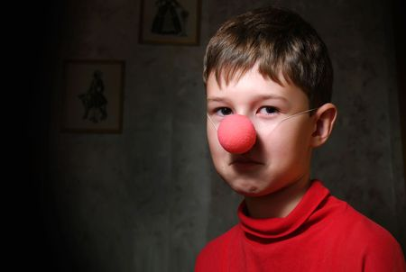 claustrophobia: The upset boy with clowns nose in dark room Stock Photo