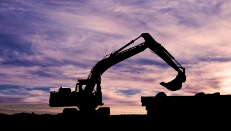 View digger working on a building site at sunset photo