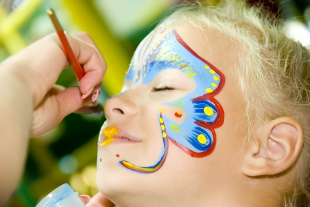 child s: Beautiful girl with blue eyes with painted butterfly on her face
