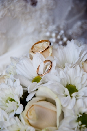 Wedding rings on the bouquet the bride on background of wedding dress photo