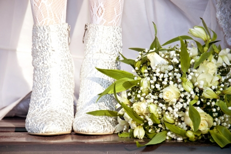 Feet of bride in in white boots next to a bouquet photo