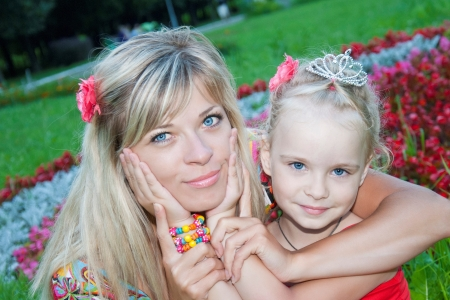 Mother and daughter hugging in summer park photo