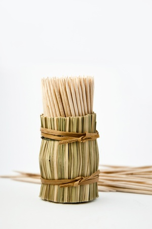 Bunch of wooden toothpick in round wattled straw holder photo