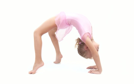 Little child gymnast making elements on a white background in the studio photo
