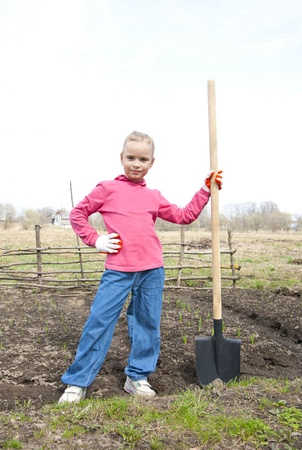 Girl in the garden with a shovel ready to dig photo