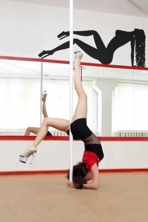 Young pole dance woman at a training class photo