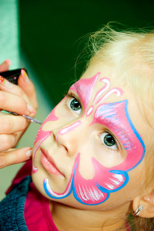 Beautiful girl with blue eyes with painted butterfly on her face photo