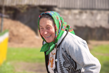 Happy old woman on his farm on a sunny day photo