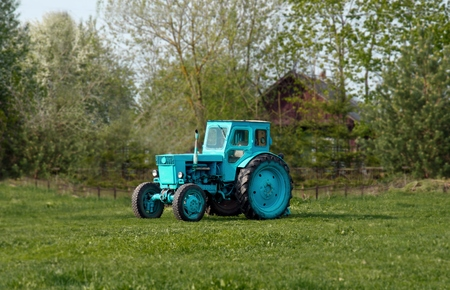 old tractor on a farm ready for a long time to help his master photo