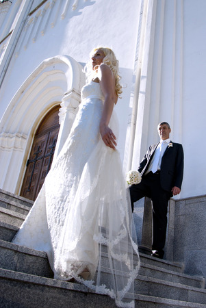 A beautiful bride and handsome groom near the church during wedding photo