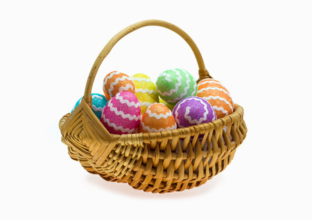 Easter basket with eggs over white background photo