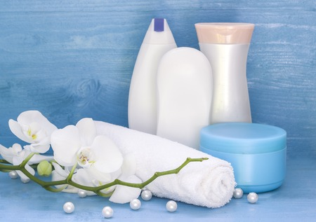 blue orchid: box of washing, white towel and orchid on the blue wooden background Stock Photo