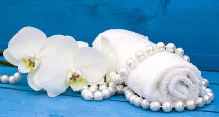 azul turqueza: centro de rehabilitación con la orquídea blanca y una toalla blanca sobre fondo de madera azul