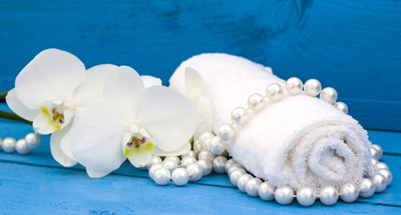 blue orchid: health spa with white orchid and white towel on blue wood background Stock Photo