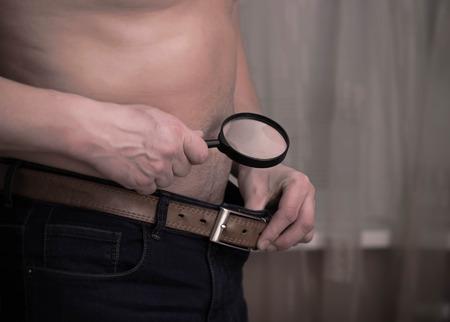 genitali: Guy avere preoccupazioni di dimensioni e check-out con una lente di ingrandimento. Salute e l'impotenza Archivio Fotografico